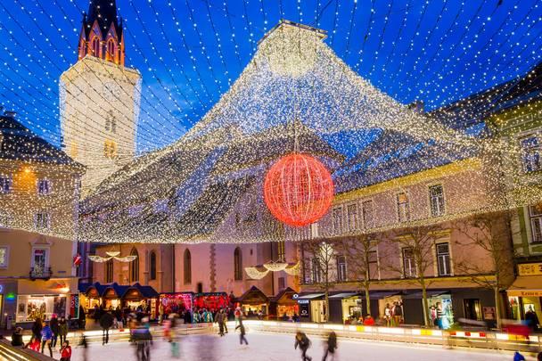 Am Abend lockt das städtische Treiben und das Eislaufen am Rathausplatz in Villach, der Stadt im Licht.